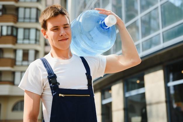 Улыбающийся доставщик, несущий бутылку с водой на плече