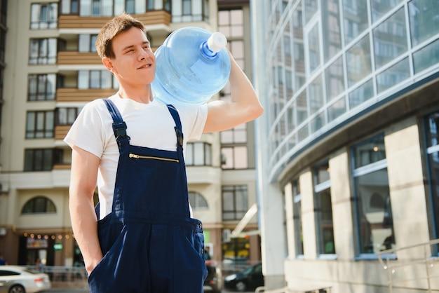 Smiling delivery man carrying water bottle on shoulder