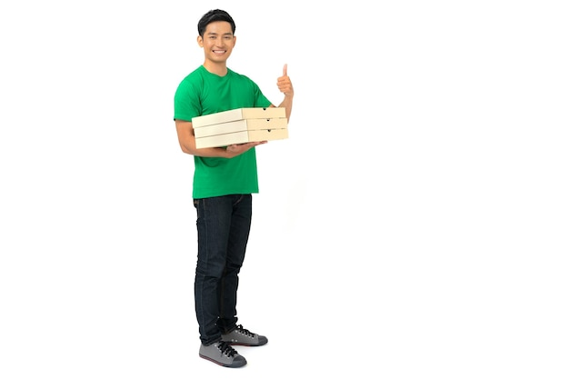 Smiling delivery man employee in blank t-shirt uniform standing with credit card giving food order and holding pizza boxes isolated