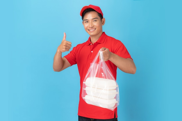 Smiling delivery man employee in red cap blank shirt uniform  standing with giving food order isolated on blue