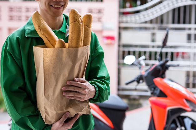 Smiling delivery man hold baguette bread in bakery paper bag to deliver customer with motorbike