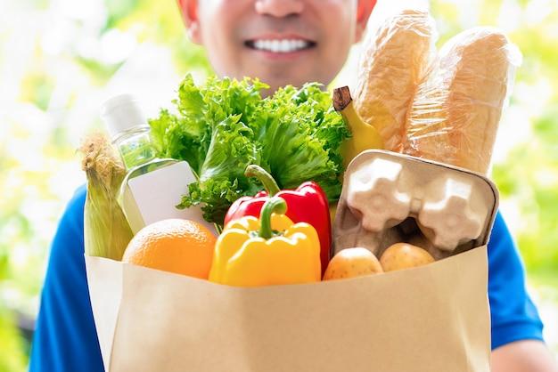 집에서 고객에게 제공 할 준비가 식료품 가방을 들고 웃는 배달 남자