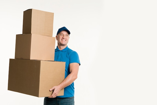 Smiling delivery man holding cardboard boxes with copy space