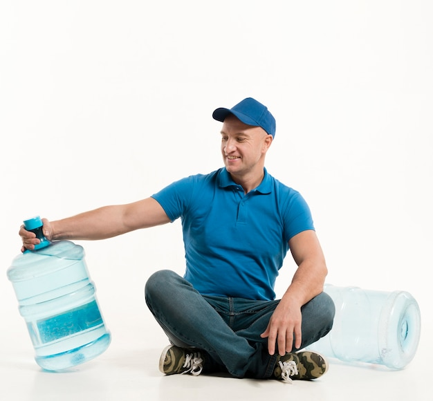 Smiling delivery man looking at water bottle