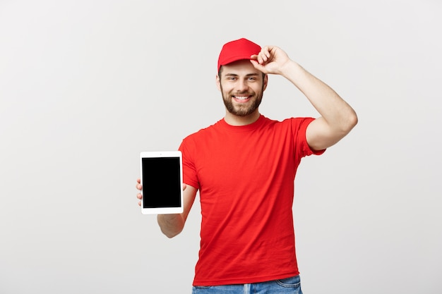 Smiling delivery man presenting tablet in his hand showing something.
