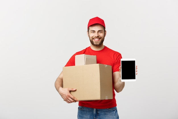Smiling delivery man presenting tablet and holding boxes in his hand.