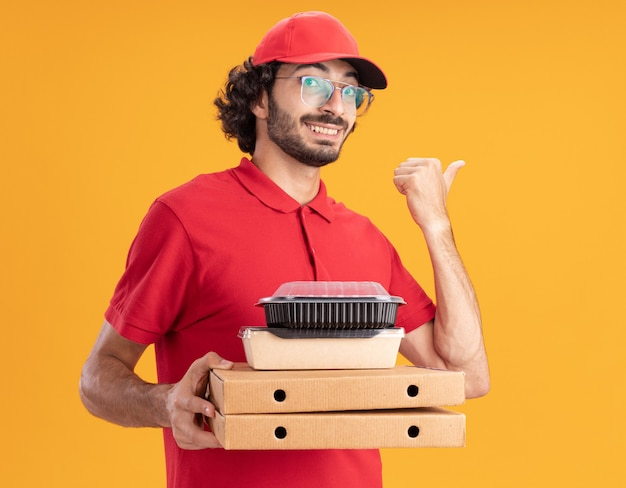 Smiling delivery man in red uniform and cap wearing glasses holding pizza packages with paper food package and food container on them looking at front pointing at side