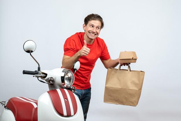 Fattorino sorridente in uniforme rossa che sta vicino al motorino e che tiene gli ordini della carta di credito che fa gesto giusto su fondo bianco