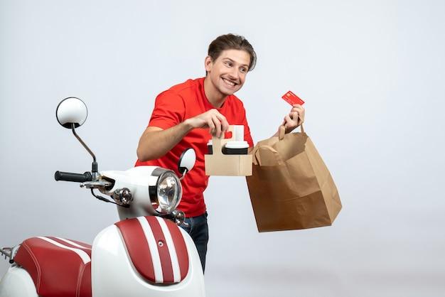 Uomo di consegna sorridente in uniforme rossa che sta vicino al motorino e che tiene gli ordini della carta di credito su fondo bianco