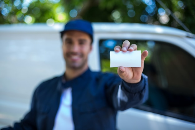 Smiling delivery man showing business card