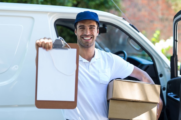 Smiling delivery man showing clipboard
