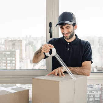 Smiling delivery man in uniform packing cardboard box