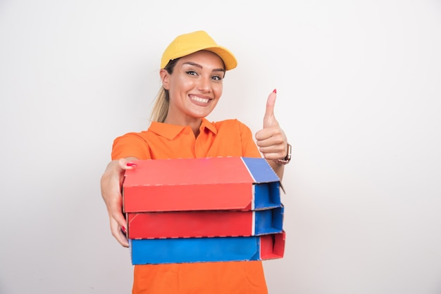 Smiling delivery woman holding pizza boxes making thumbs up.