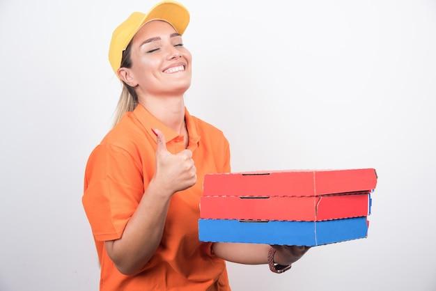 白い背景の上のピザボックスを保持している配達の女性の笑顔。