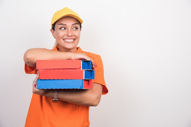 Smiling delivery woman holding pizza boxes on white background.