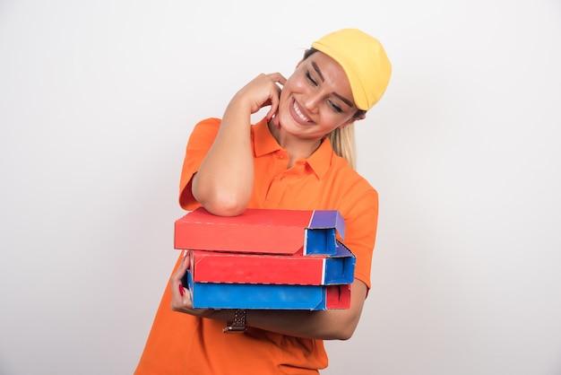 ピザの箱を持っている笑顔の配達の女性。