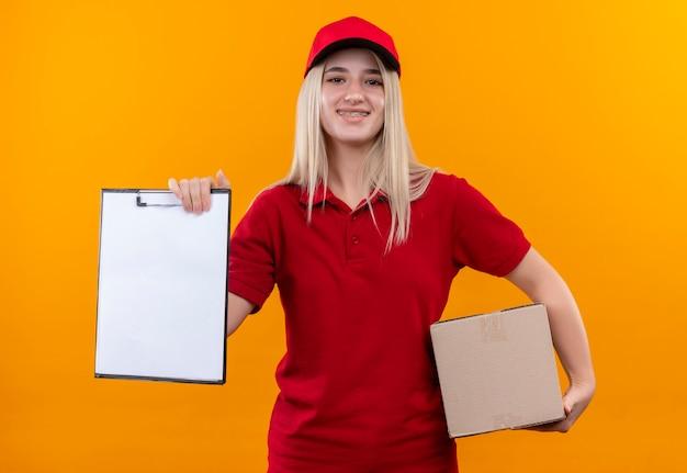 孤立したオレンジ色の背景に赤いtシャツとキャップ保持ボックスとクリップボードを身に着けている笑顔配達少女