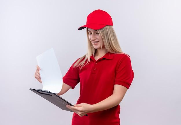 孤立した白い背景のクリップボードをめくって歯科ブレースで赤いtシャツとキャップを身に着けている笑顔の配達の若い女の子