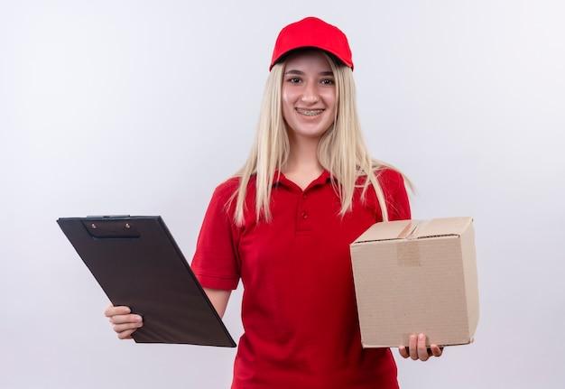 孤立した白い背景の上の歯科ブレース保持ボックスとクリップボードに赤いtシャツとキャップを身に着けている笑顔配達少女