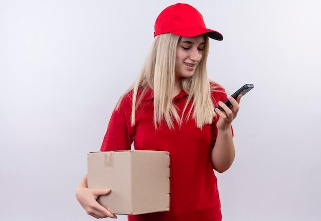 Улыбающаяся молодая девушка из службы доставки в красной футболке и кепке в зубной скобе, держащей коробку и смотрящую на телефон на руке на изолированном белом фоне