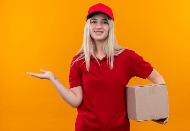 孤立したオレンジ色の背景の上の歯科用ブレース保持ボックスとポイントで赤いtシャツとキャップを身に着けている笑顔の配達の若い女の子