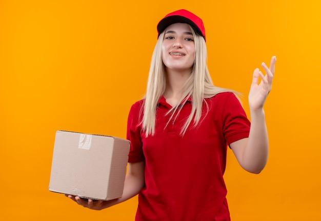 笑顔の配達の若い女の子が赤いtシャツとキャップを保持しているボックスと孤立したオレンジ色の背景に手を上げて歯科ブレース保持ボックスでキャップを着用