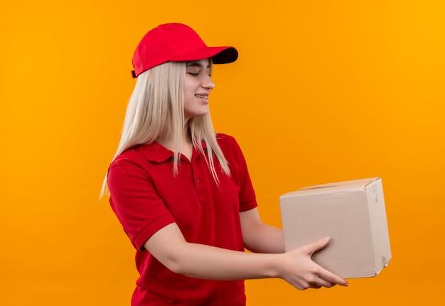 격리 된 오렌지 배경에 측면에서 상자를 들고 치과 중괄호에 빨간 t- 셔츠와 모자를 입고 배달 어린 소녀 미소