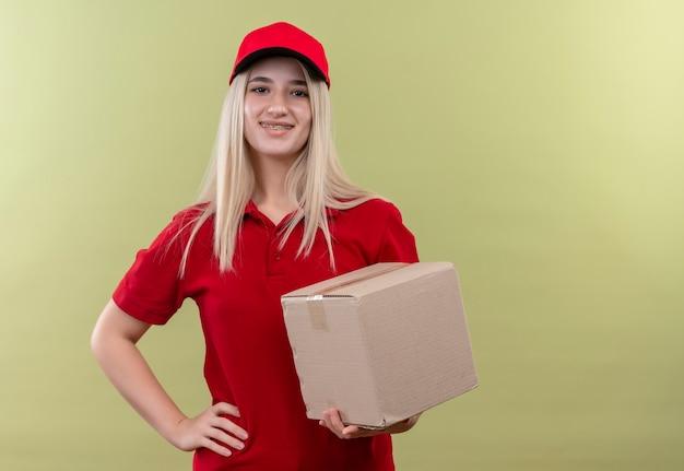 孤立した緑の背景の上の歯科ブレース保持ボックスに赤いtシャツとキャップを身に着けている笑顔の配達の若い女の子