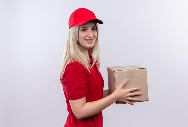 孤立した白い背景の上の歯科ブレース保持ボックスに赤いtシャツとキャップを身に着けている笑顔の配達の若い女の子