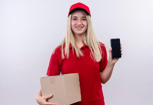 孤立した白い背景の上の電話とボックスを保持している歯科ブレースで赤いtシャツとキャップを着て笑顔
