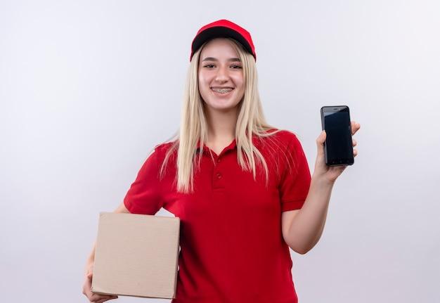 격리 된 흰색 배경에 전화 및 상자를 들고 치과 중괄호에 빨간 t- 셔츠와 모자를 입고 배달 어린 소녀 미소
