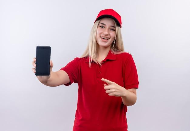 격리 된 흰색 배경에 그녀의 손에 전화에서 치과 중괄호 포인트에 빨간 티셔츠와 모자를 입고 배달 어린 소녀 미소