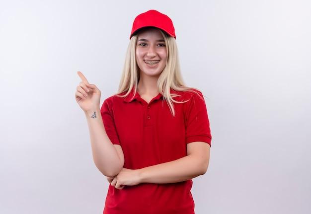 격리 된 흰색 배경에 측면 치과 중괄호 포인트에 빨간 t- 셔츠와 모자를 입고 배달 어린 소녀 미소