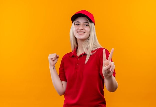 격리 된 오렌지 배경에 평화와 예 제스처를 보여주는 치과 중괄호에 빨간 티셔츠와 모자를 입고 배달 어린 소녀 미소