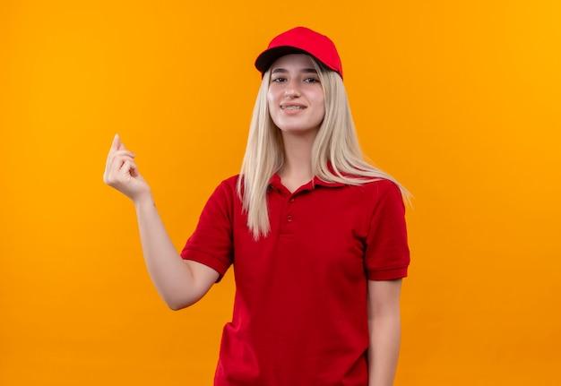 격리 된 오렌지 배경에 팁 제스처를 보여주는 치과 중괄호에 빨간 t- 셔츠와 모자를 입고 배달 어린 소녀 미소