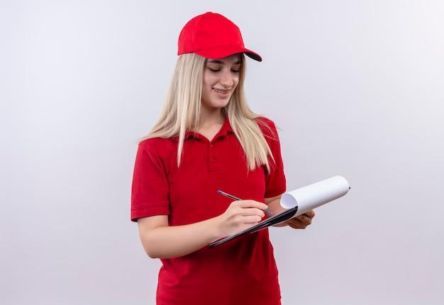 孤立した白い背景のクリップボードに書き込み中かっこで赤いtシャツとキャップを身に着けている笑顔配達少女