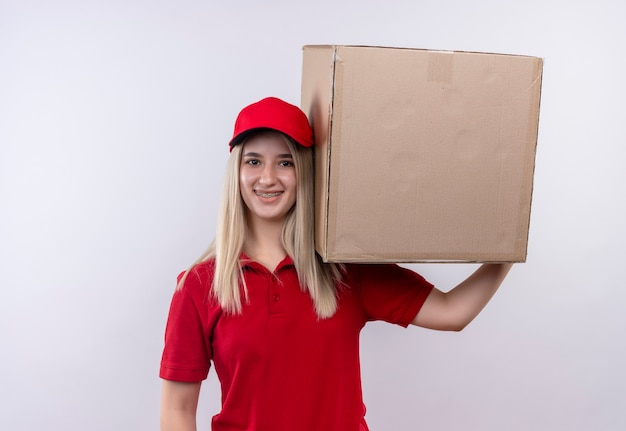 Smiling delivery young girl wearing red t-shirt and cap in dental brace holding big box on her shoulder on isolated white background