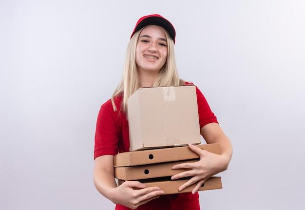 Sorridente consegna giovane ragazza che indossa la maglietta rossa e berretto in parentesi graffa dentale che tiene la scatola e la scatola della pizza su sfondo bianco isolato