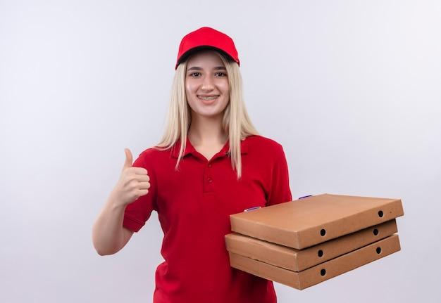 Sorridente consegna giovane ragazza che indossa la maglietta rossa e berretto in parentesi graffa dentale tenendo la scatola della pizza il pollice in alto su sfondo bianco isolato