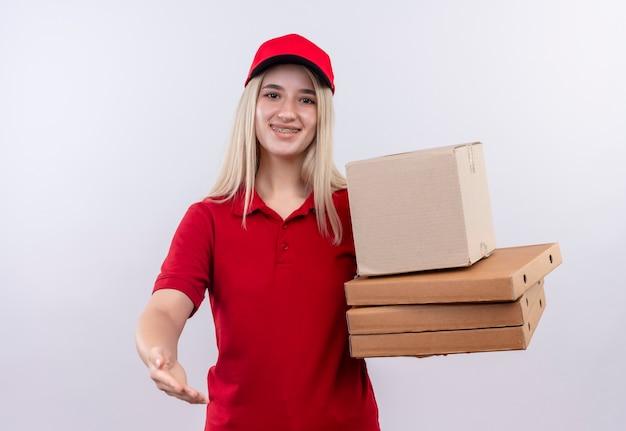 Sorridente consegna giovane ragazza che indossa la maglietta rossa e berretto in parentesi graffa dentale tenendo la scatola della pizza tendendo la mano alla telecamera su sfondo bianco isolato