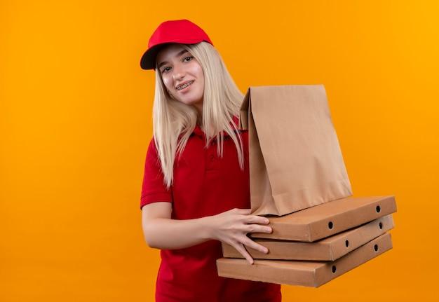 Ragazza sorridente di consegna che indossa la maglietta rossa e il cappuccio in parentesi graffa dentale che tiene la scatola della pizza e la tasca della carta su fondo arancio isolato