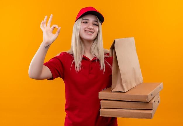 Consegna sorridente ragazza giovane indossando la t-shirt rossa e il cappuccio in tutore dentale tenendo la scatola della pizza e la tasca della carta che mostra okey gesto isolato su sfondo arancione