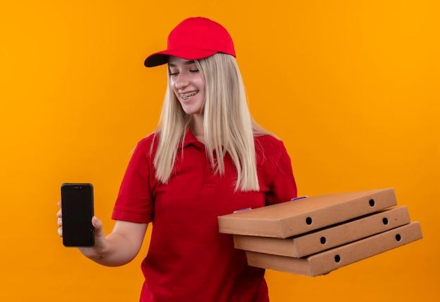 Sorridente consegna giovane ragazza che indossa la maglietta rossa e il cappuccio in parentesi graffa dentale tenendo la scatola della pizza e telefono su sfondo arancione isolato