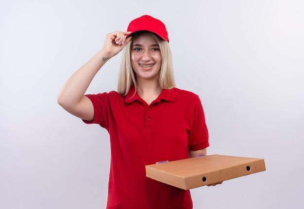 La ragazza sorridente di consegna che porta la maglietta e il cappuccio rossi in parentesi graffa dentale che tiene la scatola della pizza mise la mano sul cappuccio su fondo bianco isolato