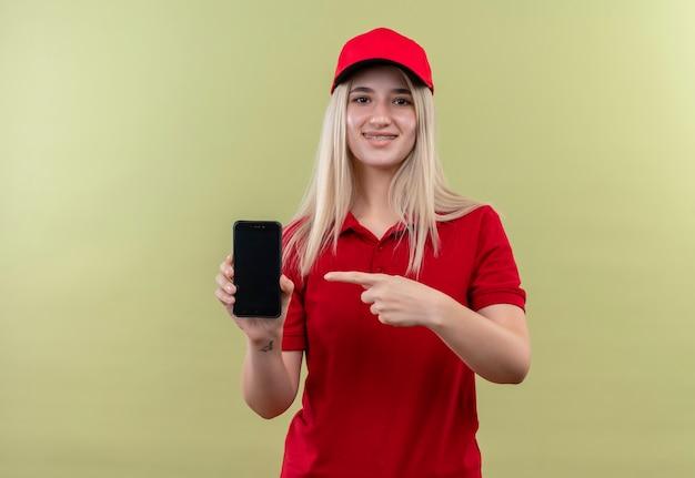 La ragazza sorridente di consegna che porta la maglietta e il berretto rossi in parentesi graffa dentale indica al telefono sulla sua mano su fondo verde isolato