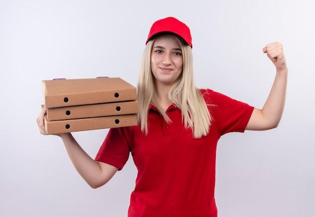 Ragazza sorridente di consegna che porta la maglietta rossa e la scatola della pizza della tenuta del cappuccio sulla sua spalla e facendo un gesto forte su fondo bianco isolato