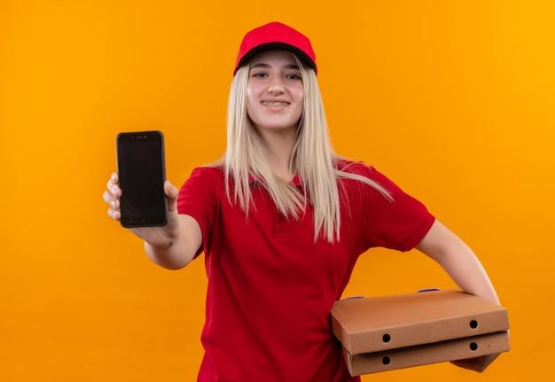 Ragazza sorridente di consegna che porta la maglietta rossa e la scatola della pizza della tenuta del cappuccio e che mostra il telefono alla macchina fotografica su fondo arancio isolato