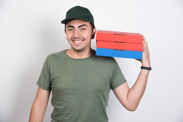 Smiling deliveryman holding three boxes of pizza on white background.