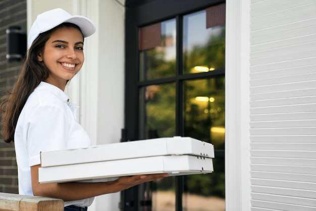 Smiling deliverywoman holding boxes of pizza