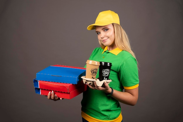 Smiling deliverywoman holding cups of coffee and cardboards of pizza. high quality photo
